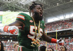 Miami linebacker Michael Pinckney celebrates with the turnover chain during the second half of an NCAA college football game against Florida State, Saturday, Oct. 6, 2018, in Miami Gardens, Fla. Miami won 28-27. (AP Photo/Lynne Sladky)