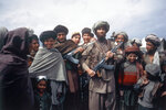 FILE - This file photo taken on April 1, 1984 shows Mujahedeen tribesmen at border camp near Wana in Afghanistan. Afghanistan is marking the 31st anniversary of the Soviet Union's last soldier leaving the country, Saturday, Feb. 15, 2020. This year's anniversary comes as the United States negotiates its own exit after 18 years of war, America's longest. (AP Photo/Christopher Gunness, File)