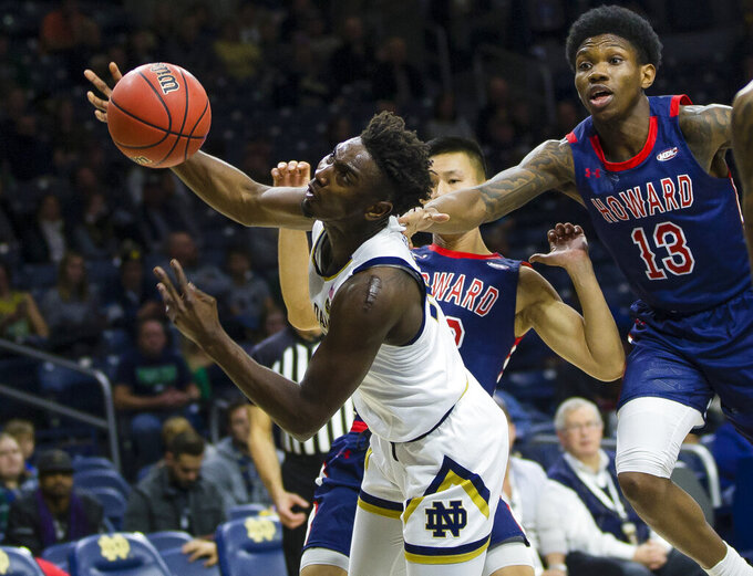 Notre Dame's Temple 'T.J.' Gibbs (10) is fouled as Howard's Ian Lee (33) and Charles Williams (13) follow him to the basket during an NCAA college basketball game Tuesday, Nov. 12, 2019 at Purcell Pavilion in South Bend, Ind. (Michael Caterina/South Bend Tribune via AP)