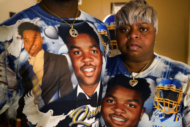 Kevin and Rontunda Moran, who lost their 17-year-old son, Jaquan Anderson, to the coronavirus, pose with T-shirts bearing his likeness, in their home in New Orleans, Wednesday, Oct. 14, 2020. Jaquan was getting ready for his senior year in high school and all the milestones that mark the beginning of adulthood — getting his driver's license, voting and heading to college. He died March 22, one of the youngest victims of the coronavirus that has largely taken the lives of older people. (AP Photo/Gerald Herbert)