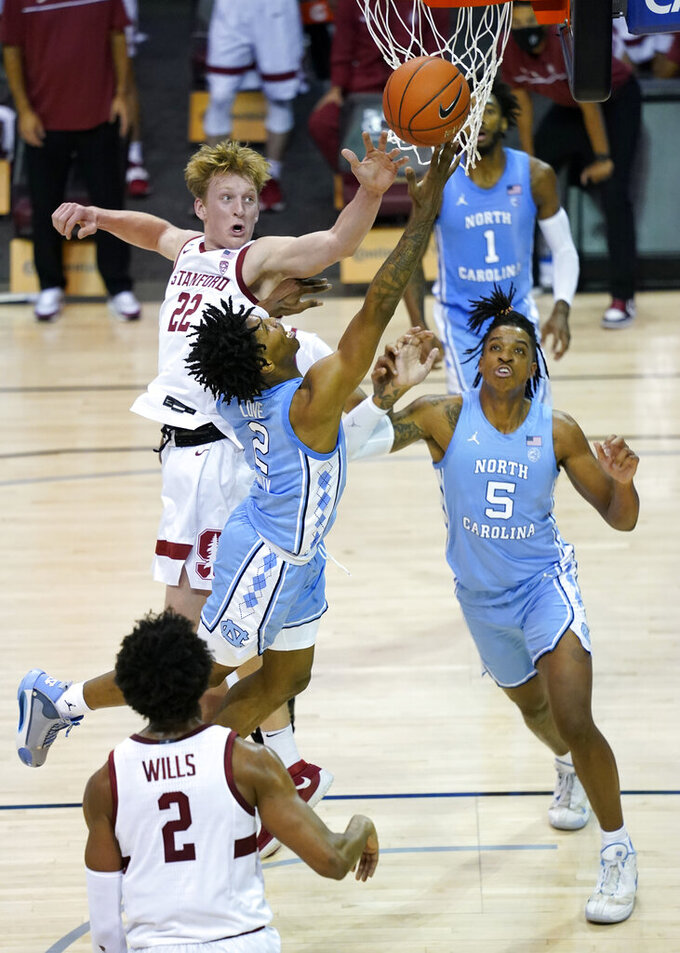 North Carolina guard Caleb Love (2) leaps to the basket past Stanford forward James Keefe (22) as North Carolina forward Armando Bacot (5) looks for the rebound in the first half of an NCAA college basketball game in the semifinals of the Maui Invitational tournament, Tuesday, Dec. 1, 2020, in Asheville, N.C. (AP Photo/Kathy Kmonicek)