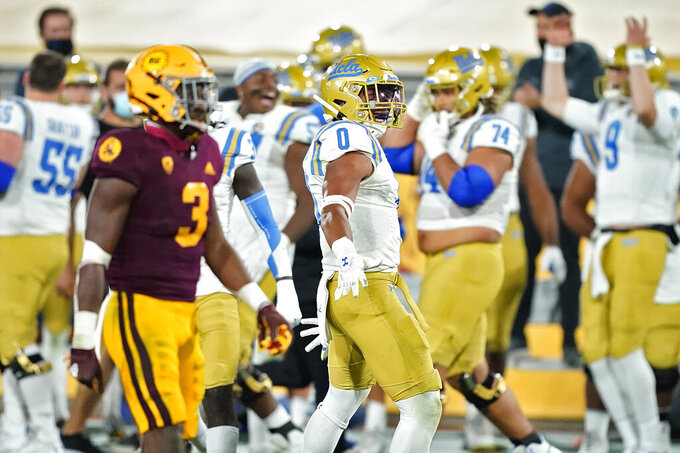 UCLA linebacker Damian Sellers (0) celebrates after Arizona State turned the ball over on downs in the final seconds during the second half of an NCAA college football game, Saturday, Dec. 5, 2020, in Tempe, Ariz. UCLA won 25-18. (AP Photo/Matt York)