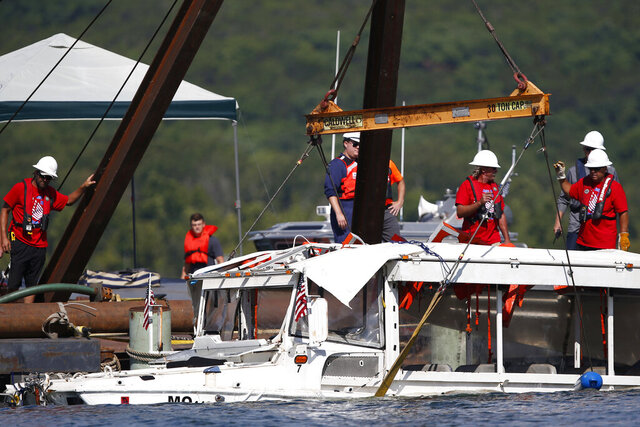 FILE - In this July 23, 2018, file photo, a duck boat that sank in Table Rock Lake in Branson, Mo., is raised after it went down the evening of July 19 after a thunderstorm generated near-hurricane strength winds. On Wednesday, Dec. 2, 2020, a federal judge has dismissed criminal indictments against three men who were charged after the tourist boat sank in a Missouri lake in 2018, killing 17 people.   (Nathan Papes/The Springfield News-Leader via AP)