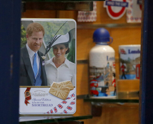 Merchandising products are seen in a shop window in Windsor, England, Thursday, Jan. 9, 2020.  In a statement Prince Harry and his wife, Meghan, said they are planning