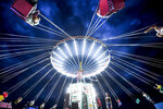 In this picture taken Saturday, Sept. 14, 2019, people enjoy a swing ride at an autumn fair in Titu, southern Romania. Romania's autumn fairs are a loud and colorful reminder that summer has come to an end and, for many families in poorer areas of the country, one of the few affordable public entertainment events of the year. (AP Photo/Andreea Alexandru)