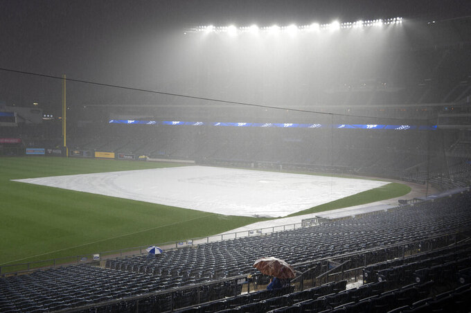 A few fans sit through a deluge at Kauffman Stadium that forced a rain delay in a baseball game between the Kansas City Royals and the Chicago White Sox, Friday, Sept. 3, 2021 in Kansas City, Mo. (AP Photo/Reed Hoffmann)