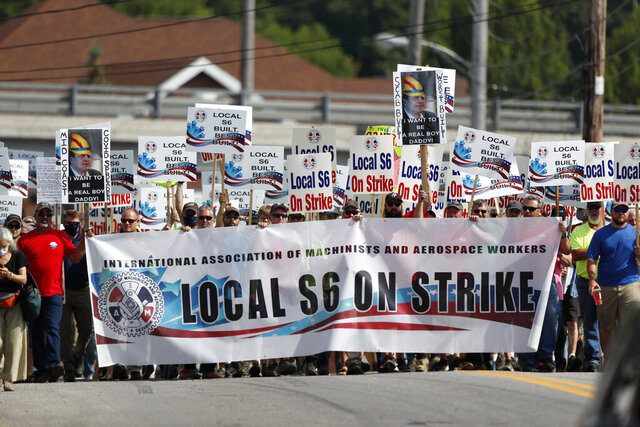 FILE - In this July 25, 2020, file photo, striking Bath Iron Works shipbuilders march in solidarity, Saturday, in Bath, Maine. The production workers went on strike June 22 after overwhelmingly rejecting the company's final contract proposal. The dispute centers on subcontractors, work rules and seniority. (AP Photo/Robert F. Bukaty, File)