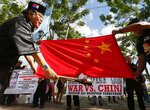 Philippine presidential candidate Elly Pamatong burns a Chinese flag in Manila, Dec. 4, 2015, to denounce China's island-building at the disputed Spratly Islands in the South China Sea. Global trade already was depressed by the 2-year-old tariff war between China and the U.S., the world's two biggest economies. Now, their rancor is spreading to include Hong Kong, Chinese Muslims, spying accusations and control of the South China Sea. (AP Photo/Bullit Marquez, File)