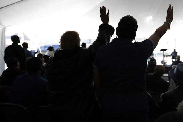 Worshippers pray during a service in a tent at Mount Bethel Missionary Baptist Church, Sunday, March 8, 2020, in Nashville, Tenn. The congregation held their Sunday service in a tent in the parking lot near the church facilities, which were heavily damaged by a tornado March 3. (AP Photo/Mark Humphrey)