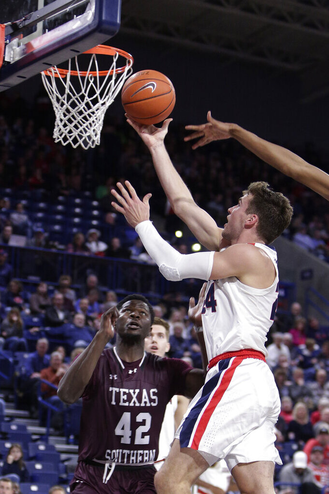 Gonzaga forward Corey Kispert, right, shoots in front of Texas Southern forward Jethro Tshisumpa during the second half of an NCAA college basketball game in Spokane, Wash., Wednesday, Dec. 4, 2019. Gonzaga won 101-62. (AP Photo/Young Kwak)