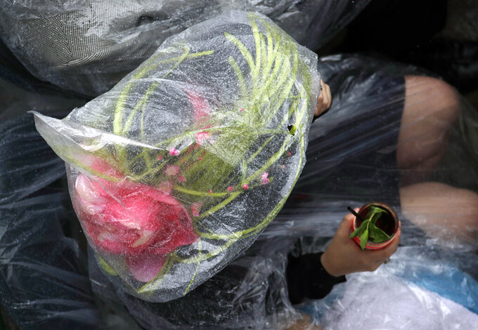 A race fan sits under the plastic cover from the rain during the 145th running of the Kentucky Derby horse race at Churchill Downs Saturday, May 4, 2019, in Louisville, Ky. (AP Photo/Charlie Riedel)