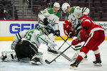 Dallas Stars goaltender Anton Khudobin (35) deflects a shot by Detroit Red Wings center Sam Gagner (89) during the second period of an NHL hockey game, Saturday, March 20, 2021, in Detroit. (AP Photo/Carlos Osorio)