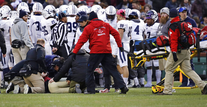 Medical workers attend to injured Harvard quarterback Tom Stewart, left, after he was tackled by Yale defensive back Miles Oldacre during the second half of an NCAA college football game at Fenway Park in Boston, Saturday, Nov. 17, 2018. Harvard defeated Yale 45-27. Stewart left the field on a stretcher. (AP Photo/Charles Krupa)