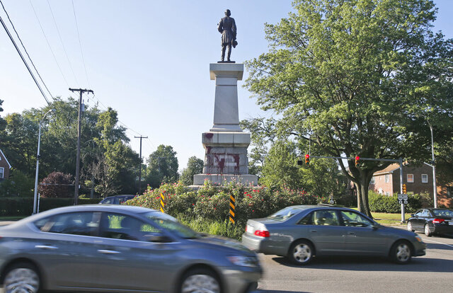 FILE - In this Aug. 22, 2018, file photo, cars pass by a statue of Confederate Gen. A.P. Hill that had been vandalized overnight in Richmond, Va. The Virginia Supreme Court has tossed out an injunction handed down by a Richmond judge that barred officials from removing the only remaining Confederate monument owned by the city. The decision could clear the way for the removal of the statue. (AP Photo/Steve Helber, File)
