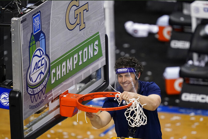 Georgia Tech head coach Josh Pastner cuts the net as he celebrates his teams 80-75 win over Florida State in the basketball Championship game of the Atlantic Coast Conference tournament in Greensboro, N.C., Saturday, March 13, 2021. (AP Photo/Gerry Broome)