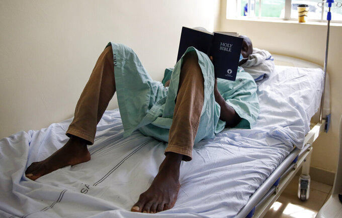 """FILE - In this Friday, May 1, 2020 file photo, a patient lies on his bed reading the Bible in a ward for those who have tested positive for the new coronavirus, at the infectious disease unit of Kenyatta National Hospital, located at Mbagathi Hospital, in Nairobi, Kenya.  More than two dozen international aid organizations have told the U.S. government they are """"increasingly alarmed"""" that """"little to no U.S. humanitarian assistance has reached those on the front lines"""" of the coronavirus pandemic as the number of new cases picks up speed in some of the world's most fragile regions. (AP Photo/Brian Inganga, File)"""