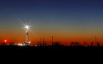 In this Thursday, April 2, 2020 photo, an oil rig lights up the horizon on the outskirts of Midland, Texas after a late sunset. (Odessa American/Eli Hartman)