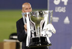 FILE - In this file photo dated July 16, 2020. Real Madrid's head coach Zinedine Zidane, holds the trophy after winning the Spanish La Liga 2019-2020 in Madrid, Spain. Zinedine Zidane is again stepping down as Real Madrid coach. The club says the Frenchman is leaving his job. It comes four days after a season in which Madrid failed to win a title for the first time in more than a decade. (AP Photo/Bernat Armangue, File)