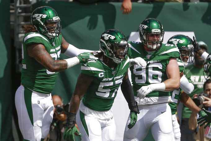FILE - In this Sept. 8, 2019, file photo, New York Jets inside linebacker C.J. Mosley (57) celebrates with teammates after running back an interception for a touchdown during the first half of an NFL football game against the Buffalo Bills, in East Rutherford, N.J. Mosley says he will play Monday night against the New England Patriots barring any setbacks at practice this week. Mosley has been sidelined since injuring his groin during the third quarter of the Jets' season-opening loss to Buffalo.  (AP Photo/Seth Wenig, File)