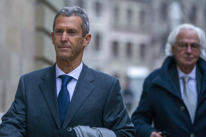 Israeli business man Beny Steinmetz, left, and his lawyer Marc Bonnant, right, arrive to a courthouse in Geneva, Switzerland, Monday, Jan. 11, 2021. Israeli diamond magnate Beny Steinmetz goes on trial in Geneva on charges of corruption and forging documents in connection with $10 million in bribes allegedly paid to a former wife of late Guinea President Lansana Conte. (Salvatore Di Nolfi/Keystone via AP)