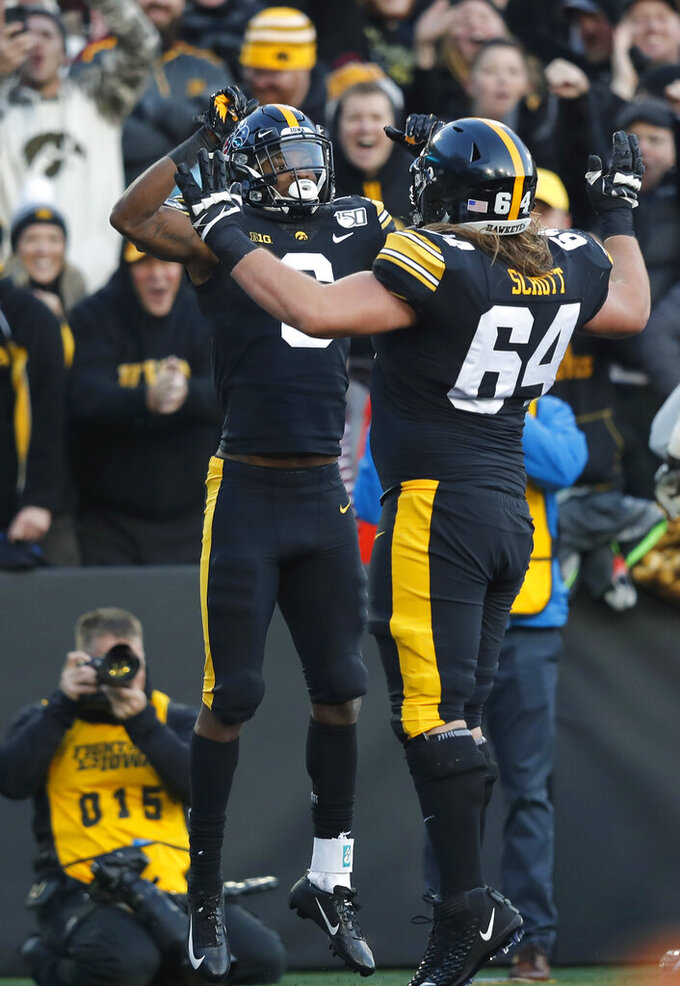 Iowa wide receiver Ihmir Smith-Marsette, left, celebrates with offensive lineman Kyler Schott, right, after scoring a touchdown during the first half of an NCAA college football game against Minnesota, Saturday, Nov. 16, 2019, in Iowa City, Iowa. (AP Photo/Matthew Putney)