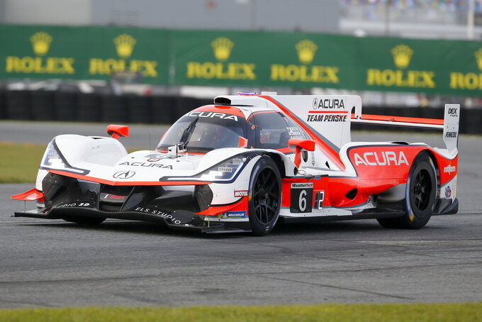 FILE - In this Jan. 23, 2020, file photo, the ACURA Team Penske (6) car driven by Juan Pablo Montoya enters the east horseshoe turn during qualifying for the Rolex 24 hour auto race at the Daytona International Speedway, in Daytona Beach Fla. The Rolex 24 begins Saturday, Jan. 25. (AP Photo/Reinhold Matay, File)