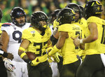 Oregon's Cyrus Habibi-Likio, center, celebrates his second-quarter touchdown against Arizona during an NCAA college football game Saturday, Nov. 16, 2019, in Eugene, Ore. (AP Photo/Chris Pietsch)