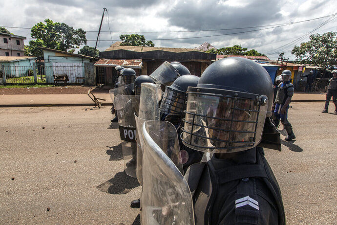Police face supporters of Guinean opposition leader Cellou Dalein Diallo in Conakry, Guinea, Wednesday, Oct. 21, 2020. Diallo declared himself winner against incumbent President Alpha Conde in Sunday's presidential elections.(AP Photo/Sadak Souici)