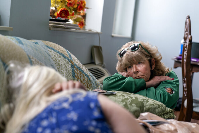 "Sue Howland, right, a member of the Quick Response Team which visits everyone who overdoses to offer help, checks in on Betty Thompson, 65, who struggles with alcohol addiction, at her apartment in Huntington, W.Va., Wednesday, March 17, 2021. ""In a way I feel empty, there's nobody here to talk to,"" Thompson said. ""I drink to escape. I try to get away from feeling."" Howland crouched next to her. ""We just need to get you back on the right path,"" she said. They told her they'd be back the next day, and that they love her. ""Who could love me?"" (AP Photo/David Goldman)"