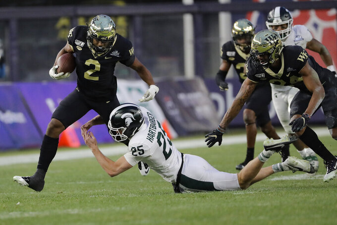 Wake Forest's Kendall Hinton (2) breaks a tackle by Michigan State's Darrell Stewart Jr. (25) during the first half of the Pinstripe Bowl NCAA college football game Friday, Dec. 27, 2019, in New York. (AP Photo/Frank Franklin II)