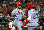 St. Louis Cardinals' Paul DeJong celebrates his solo home run with Marcell Ozuna (23) as Texas Rangers' Isiah Kiner-Falefa, rear, kneels by the plate during the ninth inning of the team's baseball game in Arlington, Texas, Saturday, May 18, 2019. The Cardinals won 8-2. (AP Photo/Tony Gutierrez)