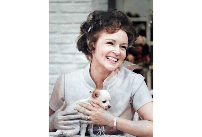 """This colorized image released by Margate And Chandler, Inc. shows actress and animal activist Betty White with a puppy from her 1970s series """"The Pet Set."""