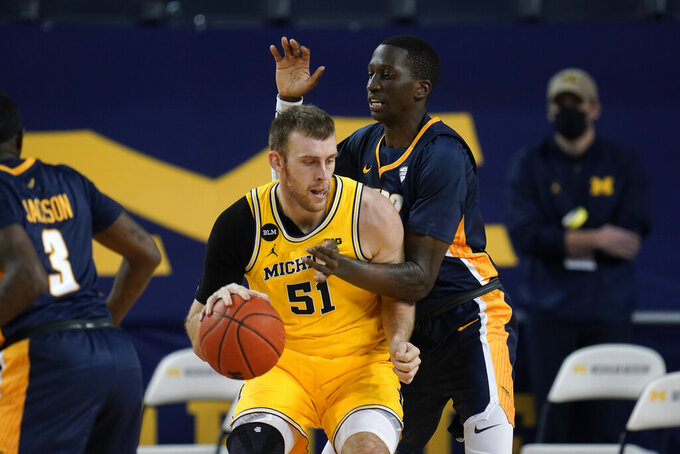 Michigan forward Austin Davis (51) drives on Toledo center Jonathan Komagum (35) in the first half of an NCAA college basketball game in Ann Arbor, Mich., Wednesday, Dec. 9, 2020. (AP Photo/Paul Sancya)