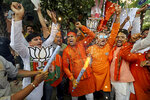 Bharatiya Janata Party (BJP) workers celebrate outside BJP headquarters in New Delhi India, Thursday, May 23, 2019. Indian Prime Minister Narendra Modi and his party have a commanding lead in early vote counting from the country's six-week general election. (AP Photo/Altaf Qadri)