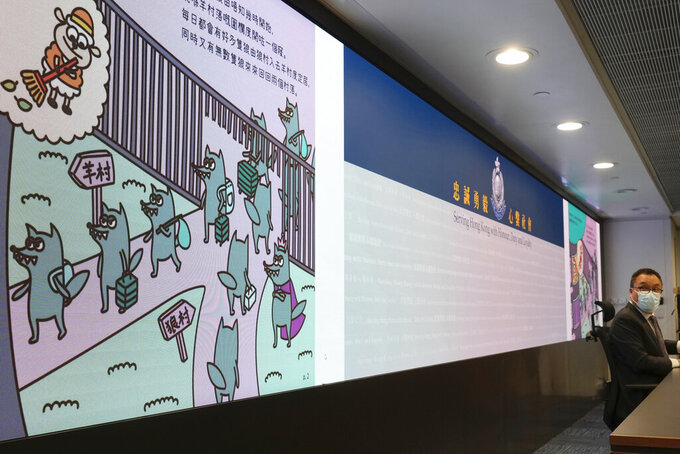 Li Kwai-wah, right, senior superintendent of Police National Security Department speaks in front of a screen showing evidence including the contents of three children's books on stories that revolve around a village of sheep which has to deal with wolves from a different village, before a press conference in Hong Kong Thursday, July 22, 2021. Hong Kong's national security police on Thursday arrested five people from a trade union of the General Association of Hong Kong Speech Therapists on suspicion of conspiring to publish and distribute seditious material, in the latest arrests made amid a crackdown on dissent in the city. (AP Photo/Vincent Yu)