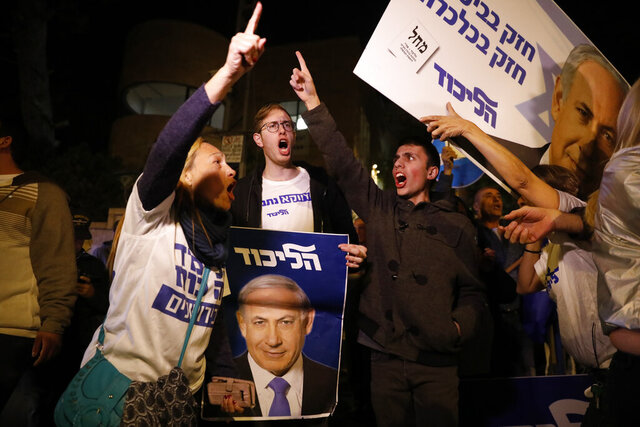 Supporters of Israeli Prime Minister Benjamin Netanyahu gather outside his residence in Jerusalem, Thursday, Nov. 21, 2019. Israel's attorney general charged Netanyahu with fraud, breach of trust and accepting bribes in three different scandals. It is the first time a sitting Israeli prime minister has been charged with a crime. (AP Photo/Ariel Schalit)