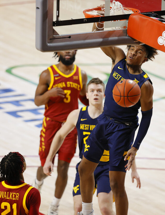 West Virginia guard Miles McBride dunks against Iowa State during the first half of an NCAA college basketball game, Tuesday, Feb. 2, 2021, in Ames, Iowa. (AP Photo/Matthew Putney)