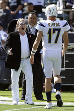 FILE - In this Oct. 15, 2017, file photo, Oakland Raiders owner Mark Davis, left, greets Los Angeles Chargers quarterback Philip Rivers (17) before an NFL football game between the Raiders and the Chargers in Oakland, Calif. From his first career start in 2006 to some riveting comebacks and crushing defeats, Chargers quarterback Philip Rivers has had plenty of memorable experiences playing against the Raiders at the Oakland Coliseum. So there will be a bit of nostalgia when Rivers plays his final scheduled game there Thursday night, Nov. 17, 2019, when the Chargers (4-5) take on the Raiders (4-4) in a game crucial for both teams' playoff hopes. (AP Photo/Ben Margot, File)