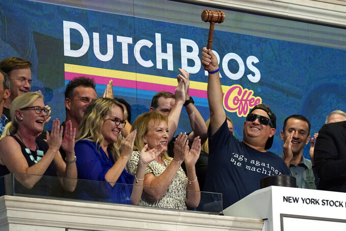 Dutch Bros Coffee Co-founder and Executive Chairman Travis Boersma, right, raises the gavel after ringing the New York Stock Exchange closing bell, Wednesday, Sept. 15, 2021. (AP Photo/Richard Drew)
