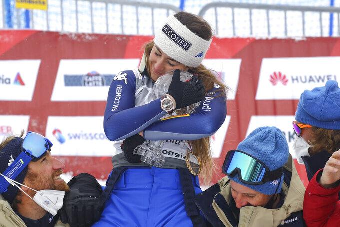 Italy's Sofia Goggia hugs the trophy of the alpine ski, women's World Cup downhill, in Lenzerheide, Switzerland, Wednesday, March 17, 2021. (AP Photo/Marco Trovati)