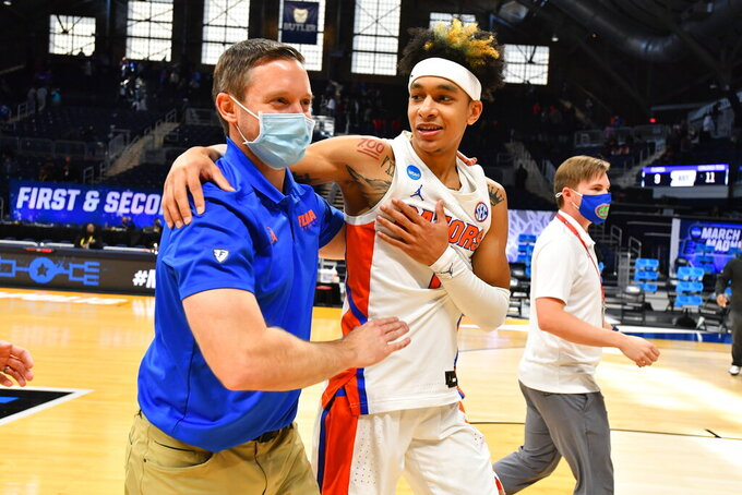Florida head coach Mike White embraces Tre Mann after they defeated Virginia Tech in a college basketball  game in the first round of the NCAA tournament at Hinkle Fieldhouse in Indianapolis, Ind., Friday, March 19, 2021.  Florida defeated Virginia 75-70. (Brett Wilhelm/Pool Photo via AP)