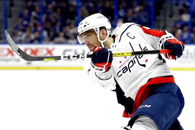 FILE - In this Dec. 14, 2019, file photo, Washington Capitals left wing Alex Ovechkin follows through on a shot against the Tampa Bay Lightning during the first period of an NHL hockey game in Tampa, Fla. Possibly losing as many as 13 games with the NHL on hold because of the coronavirus pandemic could leave Ovechkin two short of another 50-goal season and threaten his ability to break Wayne Gretzky's all-time record. (AP Photo/Chris O'Meara, File)