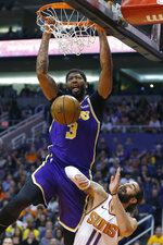 Los Angeles Lakers forward Anthony Davis dunks over Phoenix Suns guard Ricky Rubio (11) in the first half during an NBA basketball game, Tuesday, Nov. 12, 2019, in Phoenix. (AP Photo/Rick Scuteri)