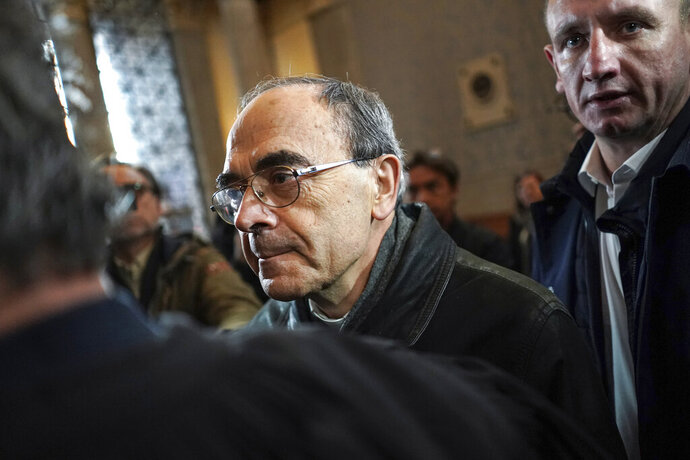 French Cardinal Philippe Barbarin, center, arrives at the Lyon courtroom for his appeal trial Thursday, Nov.28, 2019 in Lyon, central France. The French cardinal's career is on the line as an appeals court decides whether to uphold his conviction for covering up sexual abuse of children. (AP Photo/Laurent Cipriani)