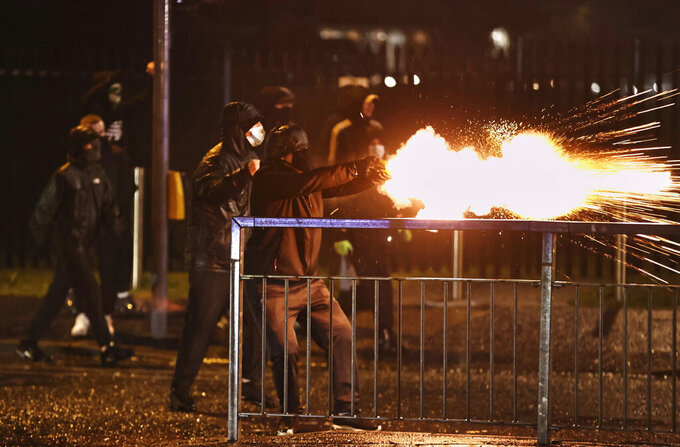 Youths fire fireworks at the PSNI on the Springfield road, during further unrest in Belfast, Northern Ireland, Thursday, April 8, 2021. Police and politicians in Northern Ireland have appealed for calm after a third night of violence that saw Protestant youths start fires and pelt officers with bricks and gasoline bombs. The flareups come amid rising tensions over post-Brexit trade rules for Northern Ireland and worsening relations between the parties in the Protestant-Catholic power-sharing Belfast government.  (Liam McBurney/PA via AP)