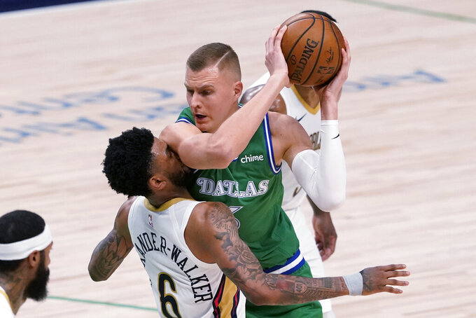New Orleans Pelicans guard Nickeil Alexander-Walker (6) takes an arm to the face while defending against Dallas Mavericks center Kristaps Porzingis during the first half of an NBA basketball game in Dallas, Wednesday, May 12, 2021. (AP Photo/Tony Gutierrez)