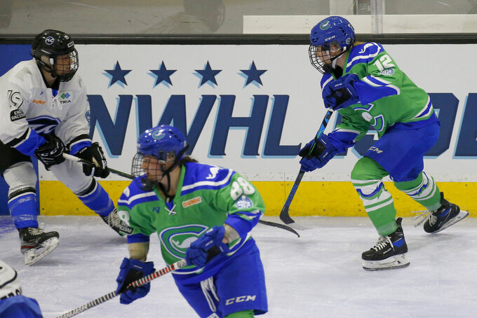 FILE - Connecticut Whale defender Maggie LaGue (12) moves the puck up the ice as Minnesota Whitecaps forward Haley Mack (19) defends during the first period of a semifinal in the NWHL Isobel Cup hockey tournament in Boston, in this Friday, March 26, 2021, file photo. The National Women's Hockey League made a potentially game-changing decision for the sport in approving to double its salary cap to $300,000 for each of its six teams on Wednesday, April 28, 2021, based on projections it is making strides in achieving financial stability entering its seventh season.(AP Photo/Mary Schwalm, File)