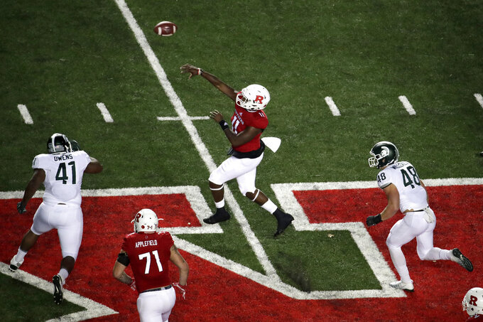 Rutgers quarterback Johnathan Lewis, center, throws a touchdown pass to running back Raheem Blackshear (not shown) as Michigan State defensive lineman Gerald Owens (41) and defensive end Kenny Willekes (48) try to get to him during the first half of an NCAA college football game, Saturday, Nov. 25, 2017, in Piscataway, N.J. (AP Photo/Julio Cortez)