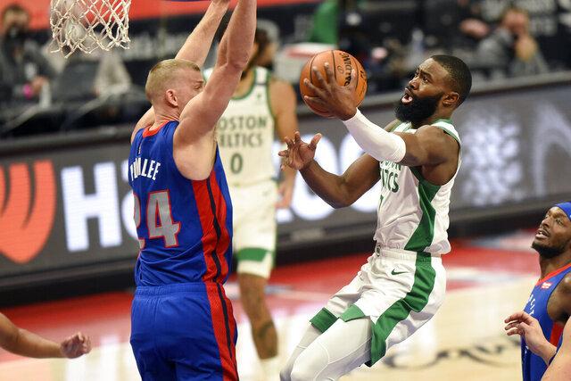 Boston Celtics guard Jaylen Brown, right, drives against Detroit Pistons center Mason Plumlee during the first half of an NBA basketball game Sunday, Jan. 3, 2021, in Detroit. (AP Photo/Jose Juarez)