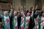 FILE - In this Dec. 21, 2011 file photo, anti-Syrian regime protesters flash the victory sign as they wear Syrian revolution flags during a demonstration in the Baba Amr area, in Homs province, Syria. The Syria Justice and Accountability Center, a Washington-based Syrian rights group said in a report, released Tuesday, May 21, 2019, that thousands of documents collected from abandoned Syrian government offices reveal the reach of President Bashar Assad's security agencies, offering a rare glimpse into the inner workings of his secretive apparatus. The documents include handwritten notes from top commanders to